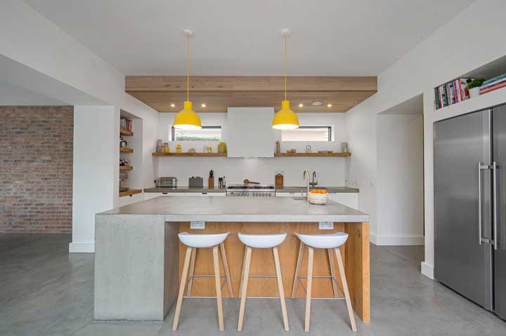 Ou na decoração da cozinha. O ponto de destaque fica por conta de alguns elementos feitos de madeira e a luminária amarela.