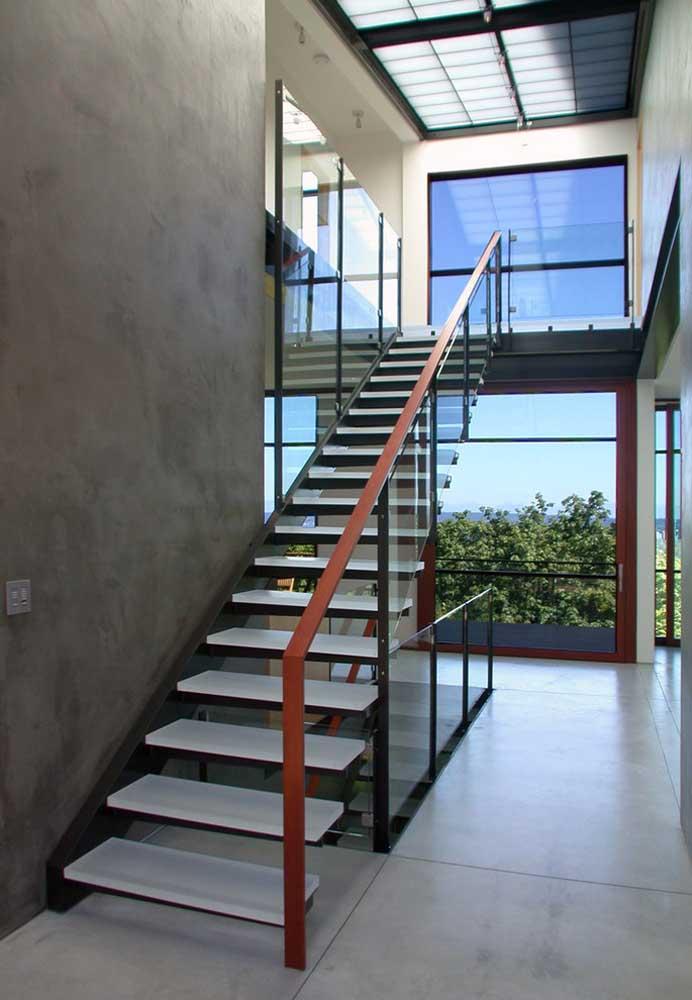 Uma boa opção é usar o cimento queimado nas paredes de mais destaque da casa. Nesse caso, foi usado na parede da escada.