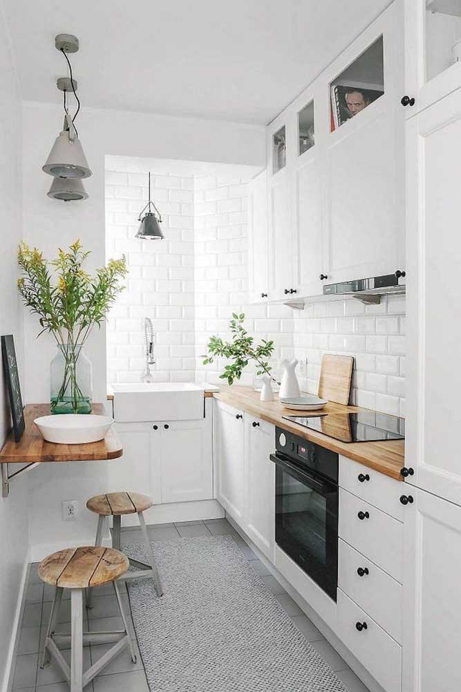 Cozinha planejada pequena de canto branca com bancada em madeira; destaque para os charmosos detalhes em preto