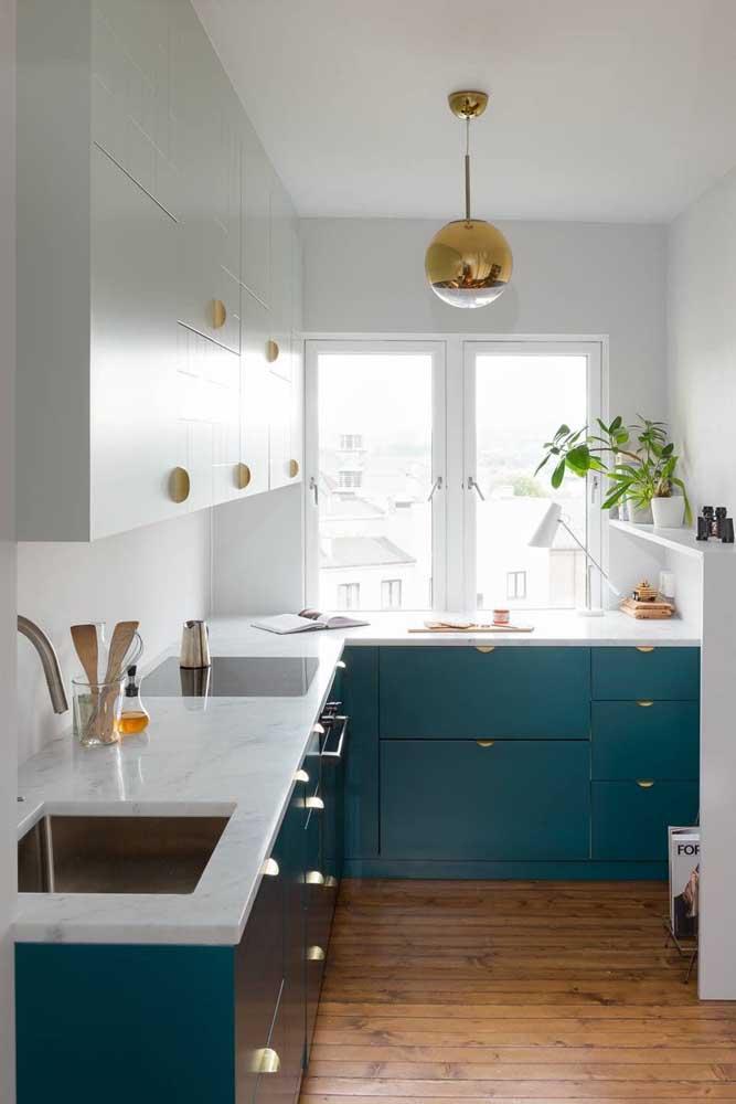 O branco dos armários junto à janela favorece a iluminação da cozinha; destaque para a bancada de mármore