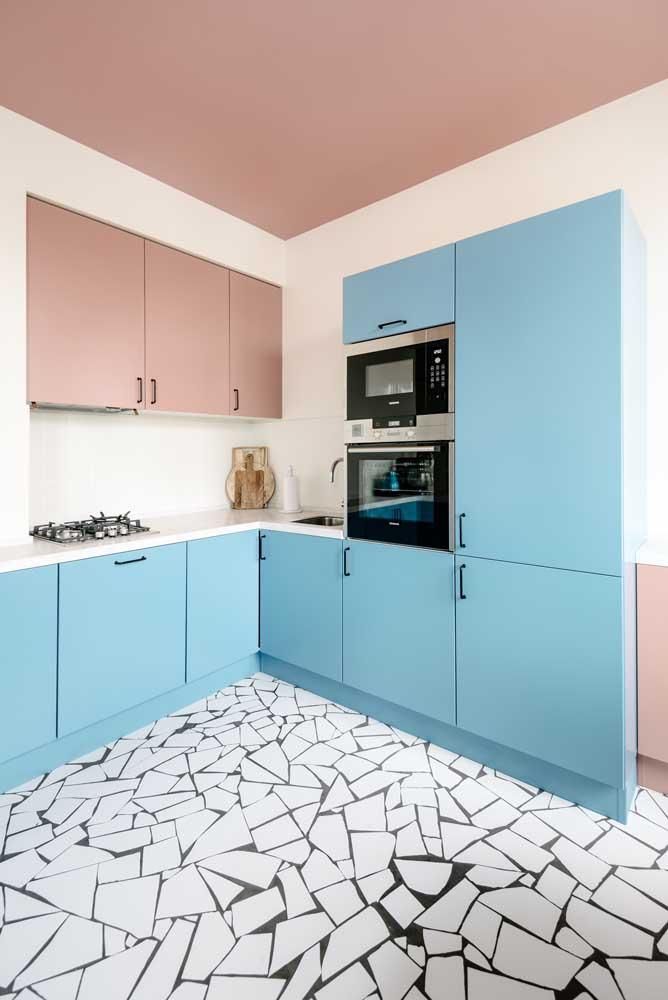 Armários rosa e azul para uma cozinha planejada de influência retrô; aqui o forno e o micro-ondas receberam um espaço exclusivo entre os móveis