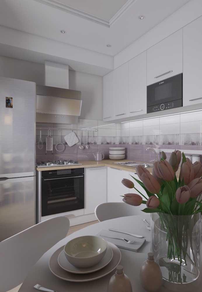 Cozinha pequena planejada branca integrada à sala de jantar; a bancada em madeira traz um fogão embutido