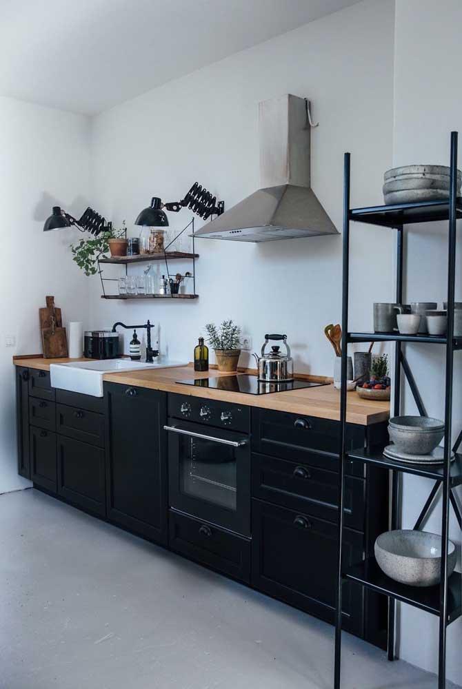 A cozinha com armários pretos e bancada em madeira remete a um estilo industrial e moderno