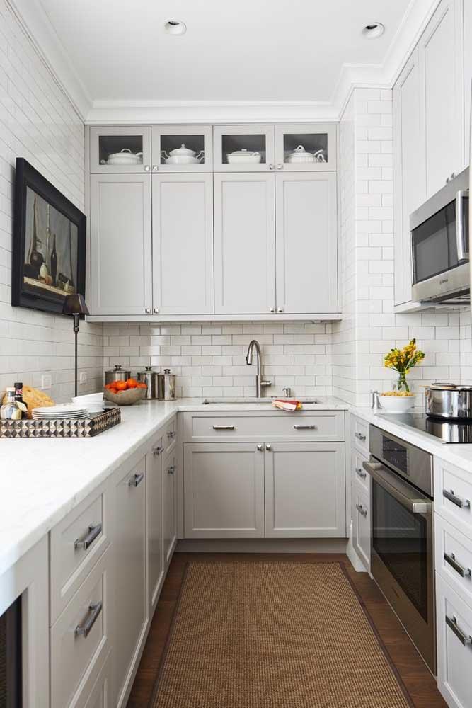 Quadro, tapete e outros elementos decorativos trazem vida à cozinha pequena planejada