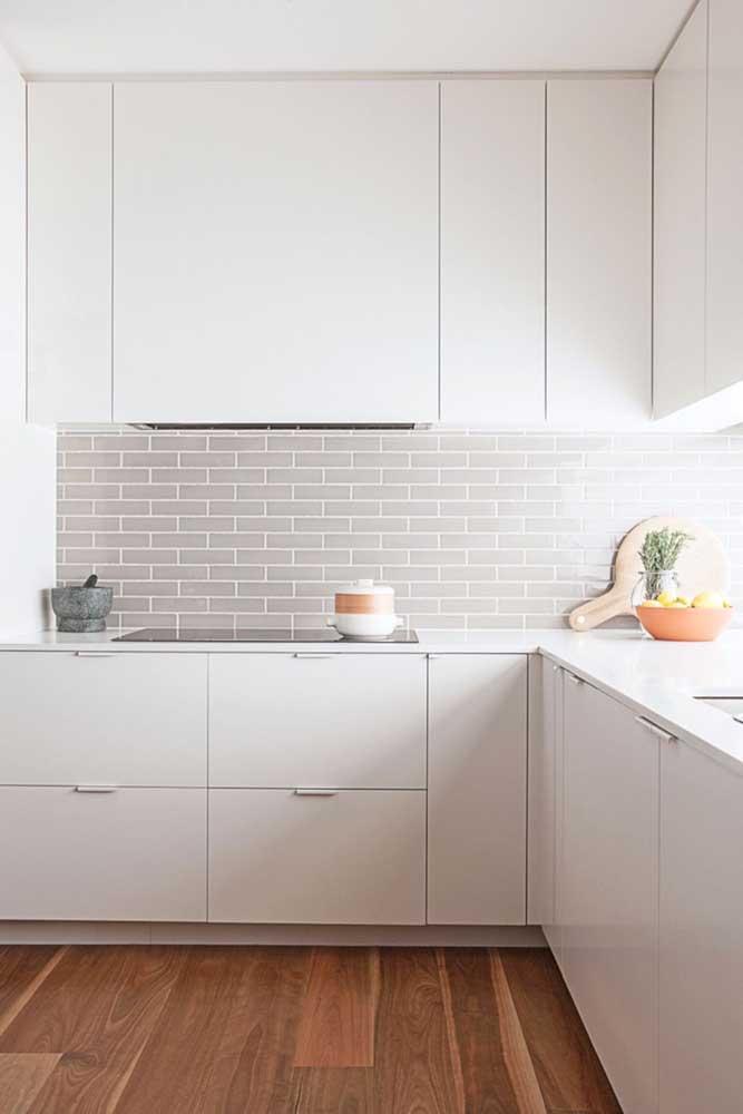 Com design minimalista, essa cozinha planejada de canto aproveita o espaço com armários maiores