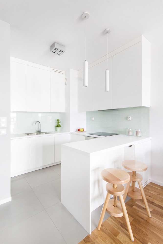 As banquetas de madeira quebram a brancura dessa pequena cozinha branca
