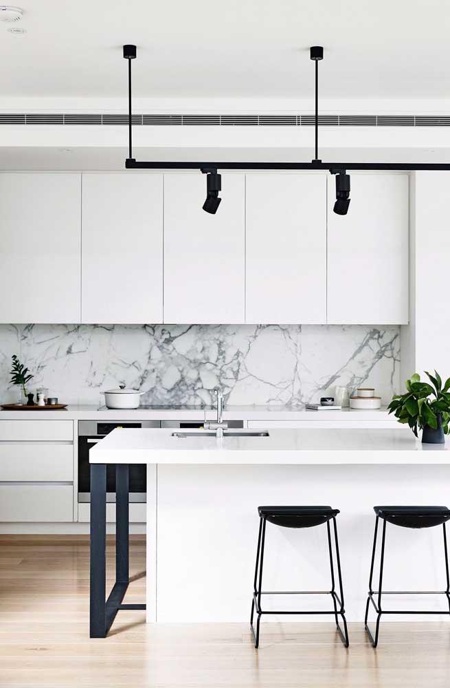 Cozinha americana com pia acoplada ao balcão; o revestimento de mármore garante o toque de sofisticação ao espaço
