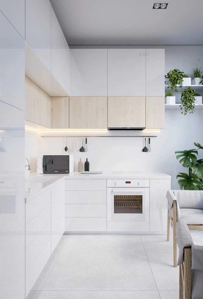 Cozinha pequena planejada em L com gavetas na bancada e fogão embutido; destaque para a iluminação sob o armário