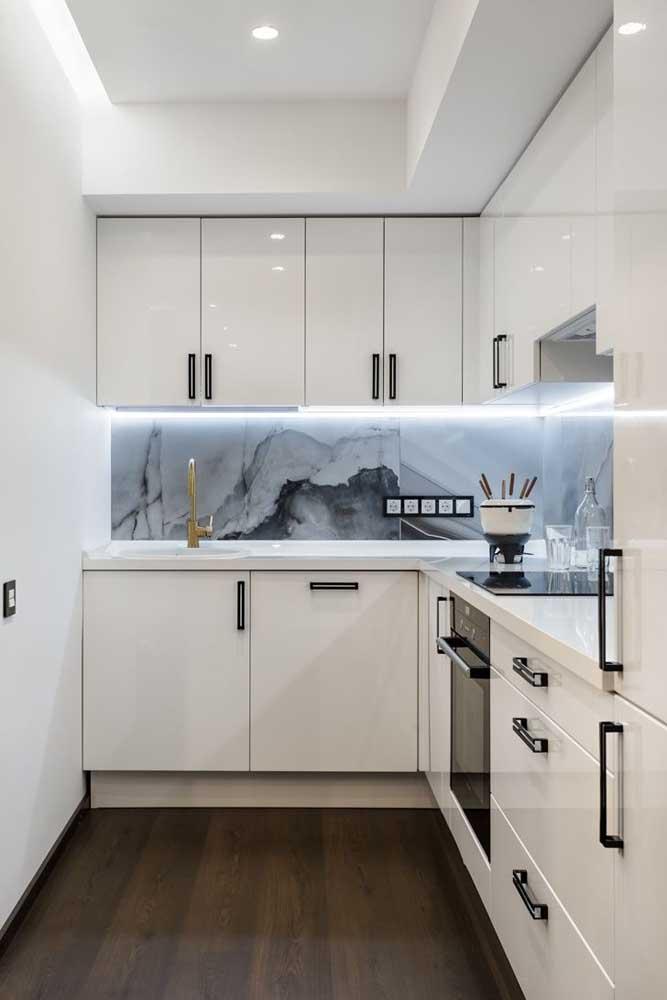 A iluminação abaixo dos armários aéreos é o grande destaque dessa cozinha planejada