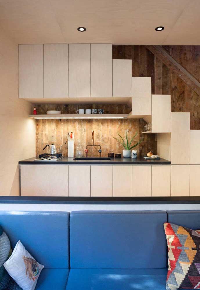 A escada também entrou na brincadeira e ganhou parte dos armários da cozinha planejada
