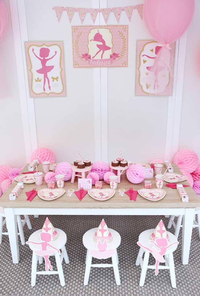 Uma boa opção decorativa é fazer um painel com vários quadros de bailarina, seguindo a mesma decoração da mesa.