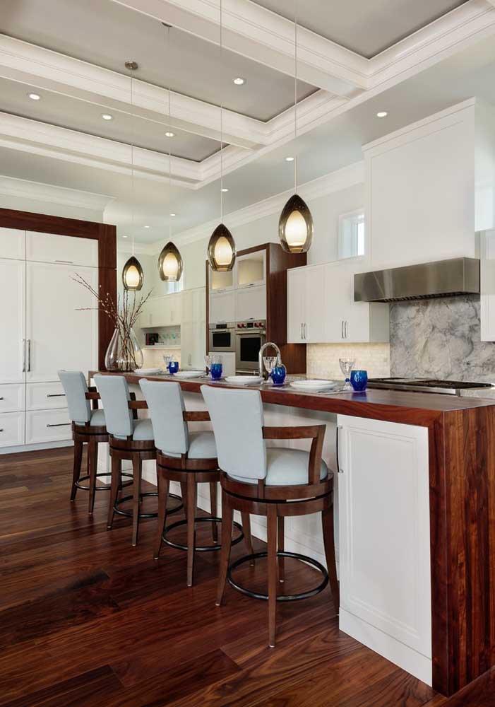 O extenso balcão da cozinha ganhou a companhia de um teto cheio de estilo, com lindas molduras em gesso