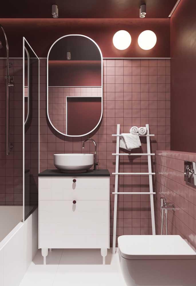 O banheiro em tons de vermelho recebeu o contraste do pequeno gabinete branco
