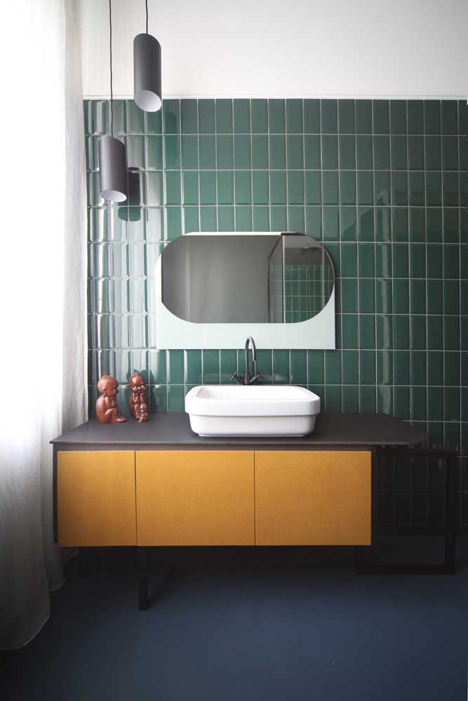 Que tal investir em um banheiro de cores complementares? Aqui, o amarelo, complementar ao azul e verde, ganhou espaço no gabinete