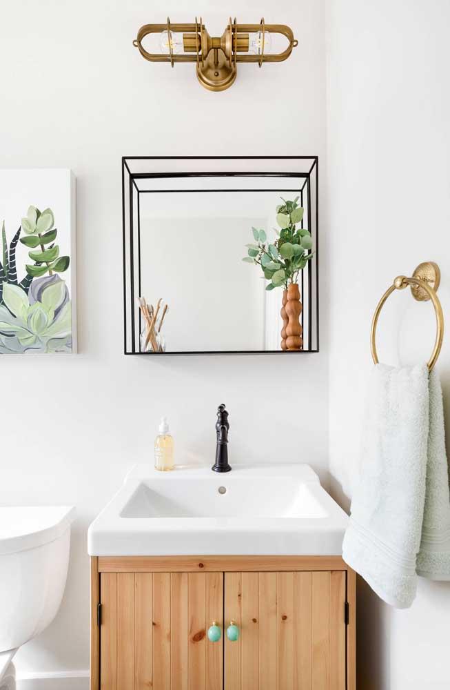 Para esse banheiro de influência escandinava, a opção foi por um gabinete simples, de madeira clara, destacado pelos puxadores azul claro