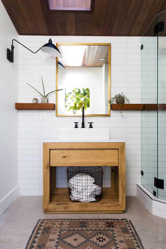 A moldura do espelho, apesar de dourada, combina com o tom da madeira usada no gabinete