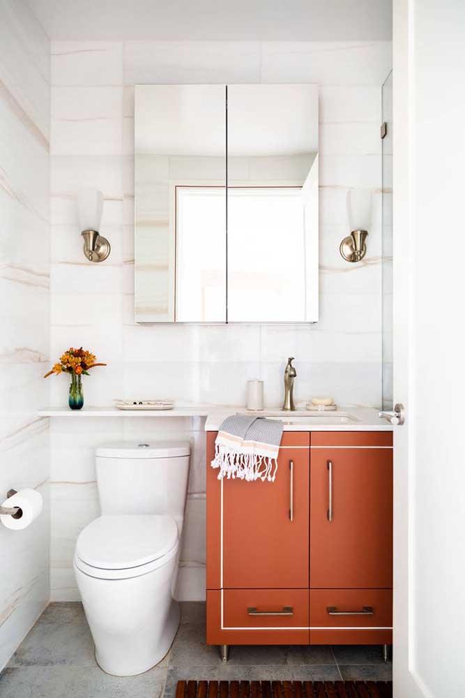 O gabinete laranja soube como entrar na decoração clean desse banheiro se ajustando com muito estilo ao projeto