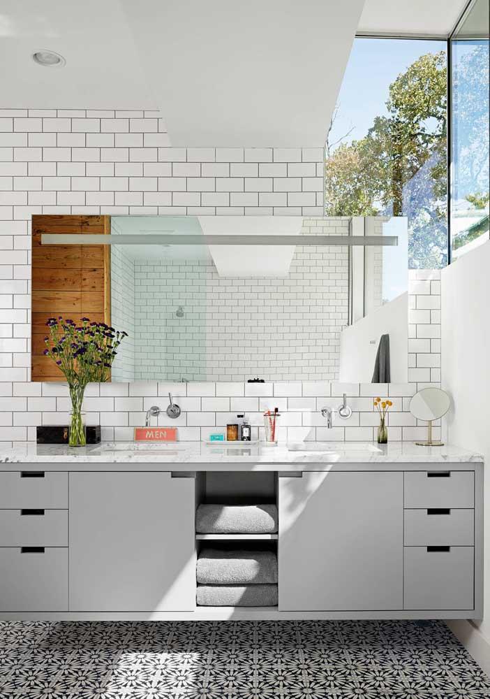O gabinete de design simples ganhou destaque nesse banheiro rico em detalhes no chão e na parede