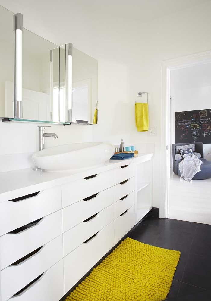 O gabinete branco desse banheiro ganhou o contraste da toalha e do tapete amarelo ouro