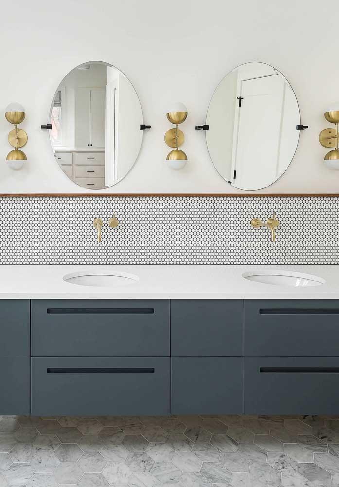 O elegante e charmoso azul petróleo se destaca nesse gabinete de banheiro branco; repare como as torneiras douradas completam o projeto