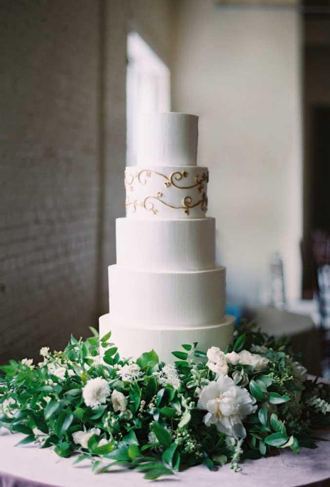 O bolo de casamento pode ser algo mais tradicional como esse modelo que leva vários andares. Para decorar é aconselhável colocar apenas um detalhe que contraste com o fundo branco.