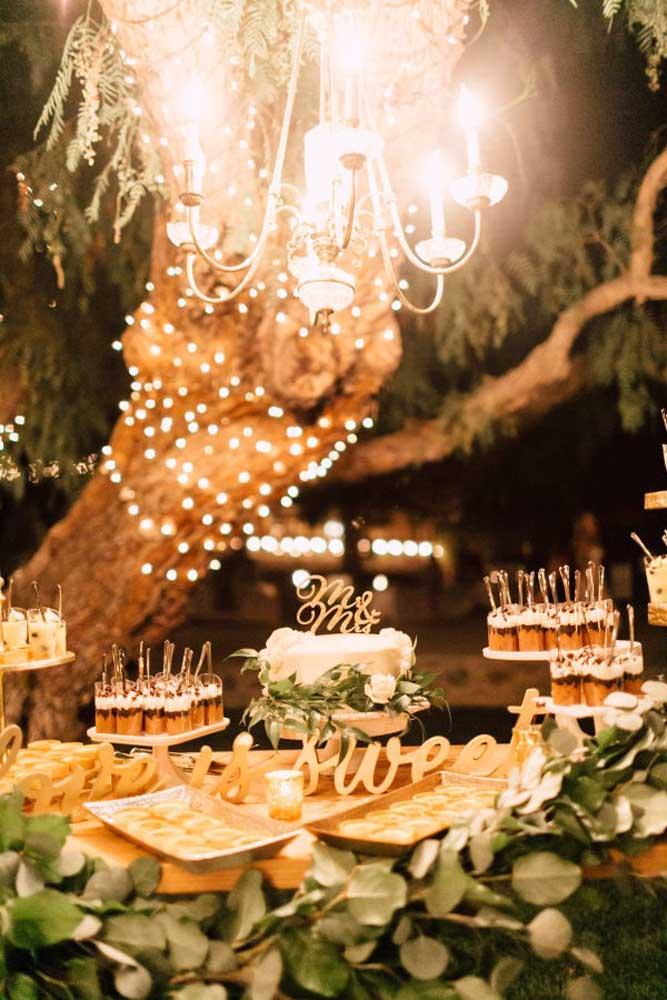 Se você optar por um bolo simples, é importante fazer uma bela decoração na mesa do bolo para complementar o cenário. Para chamar atenção, aposte em um belo lustre para ficar pendurado na direção da mesa.