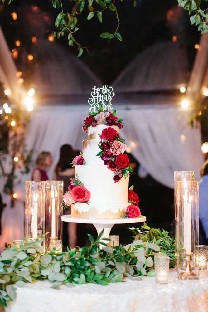 Que tal fazer um bolo com arranjo de flores vermelhas? Mais romântico que isso é impossível. A vela dá o toque todo especial para a decoração da mesa.