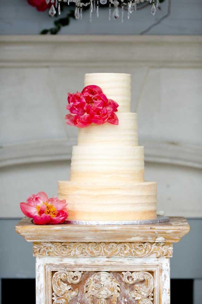 Quem prefere um bolo tradicional totalmente branco, pode dar uma quebrada na cor colocando um pequeno arranjo de flores em tons mais vivos. Nesse caso, para não chamar tanto a atenção, coloque o bolo em uma mesa feita só para ele