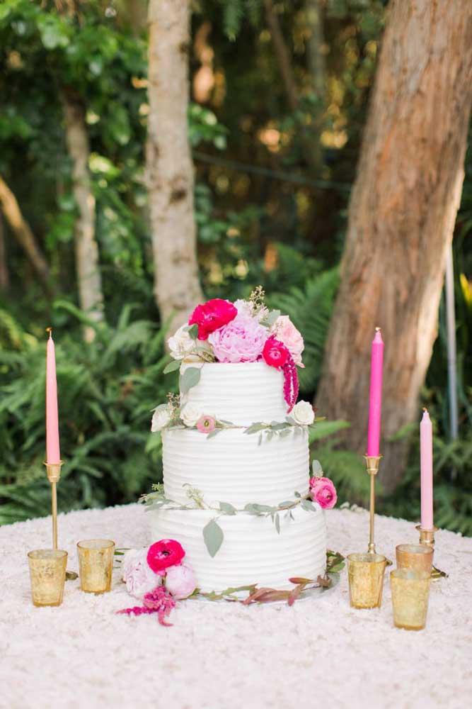 Em uma festa ao ar livre e de dia, você pode optar por um bolo mais simples com andares e decorar a mesa apenas com velas colocadas em castiçais.
