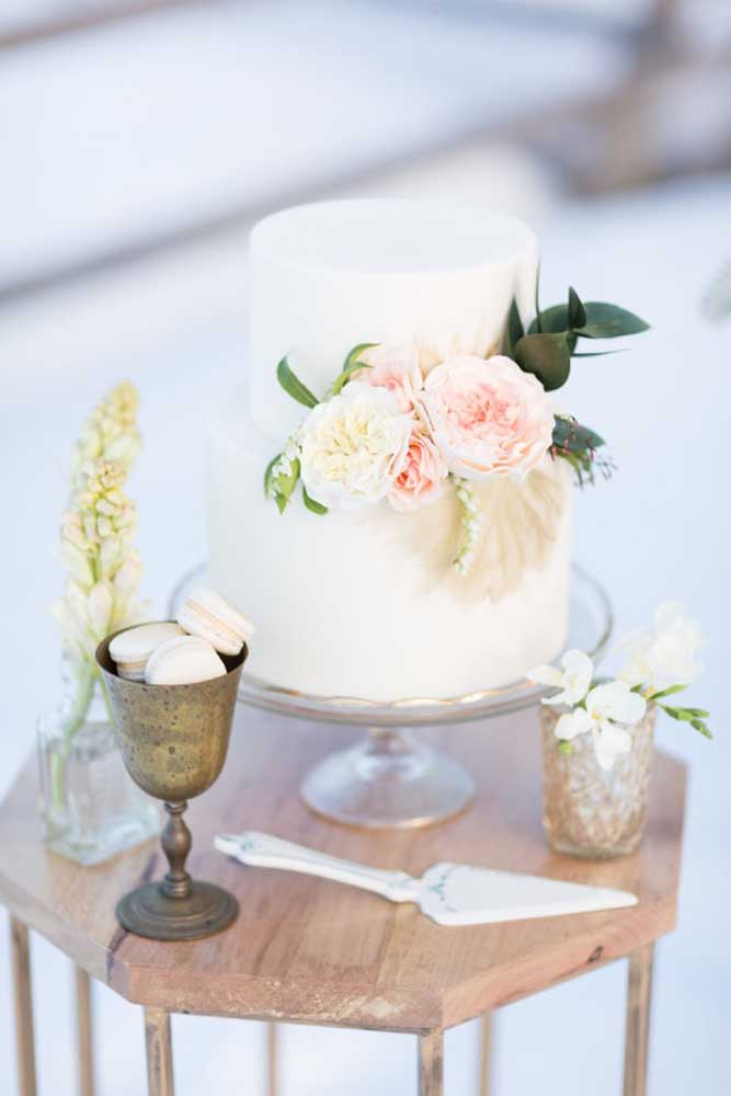 A mesa do bolo de casamento não precisa ser cheia de detalhes, basta usar elementos que combinem com a decoração.