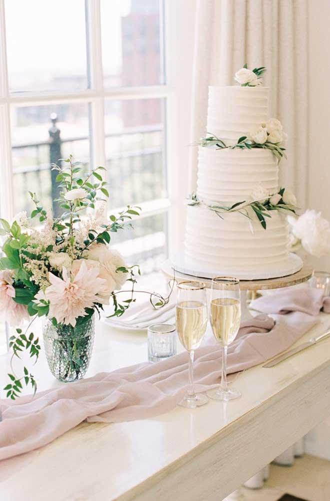A mesa do bolo de casamento pode ser colocada próximo à janela para receber uma iluminação natural, já que a decoração é mais leve.