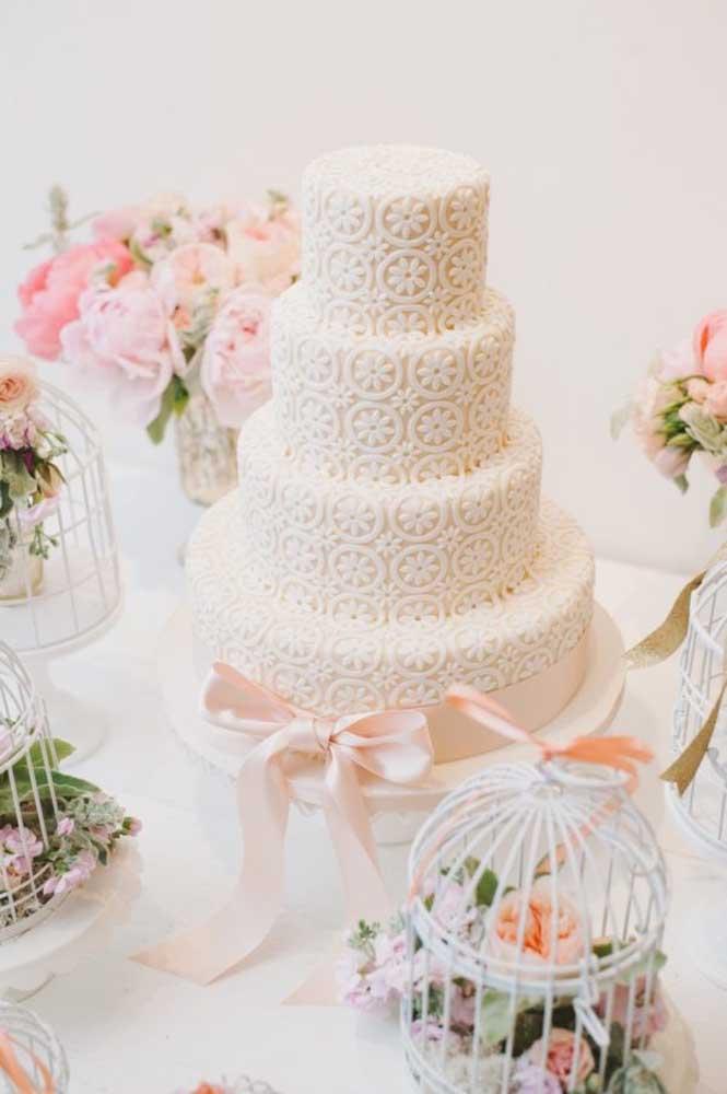 Já pensou em fazer um bolo de noiva com detalhes que mais parecem renda? Para acompanhar a decoração, na mesa você pode colocar algumas gaiolas com arranjos de flores. O efeito é incrível!