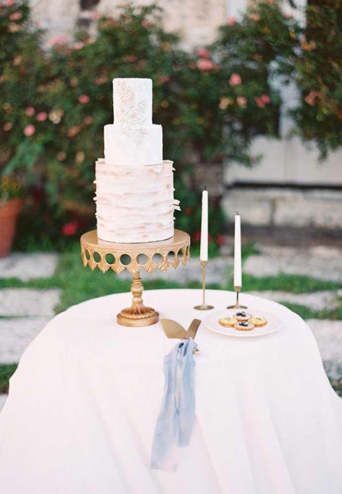 Escolha uma base requintada para colocar o bolo de casamento. A decoração da mesa pode ser mais simples, mas a vela não pode faltar.