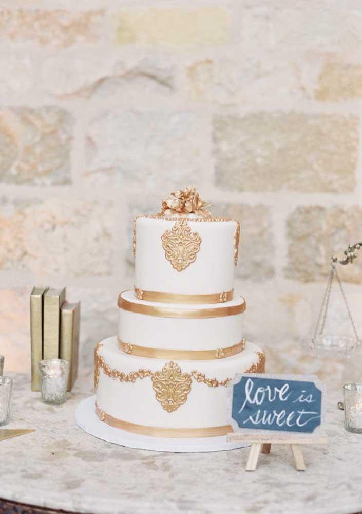 Se você gosta de um pouco mais de pompa, nada melhor do que decorar o bolo com detalhes em dourado que remetem aos brasões da família. Mas aposte em uma mesa sem muitos detalhes para não tirar o brilho do bolo.