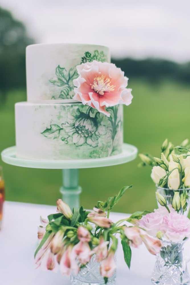 Que tal fazer alguns desenhos de flores no bolo? Dê preferência para o mesmo modelo que será usado no arranjo.