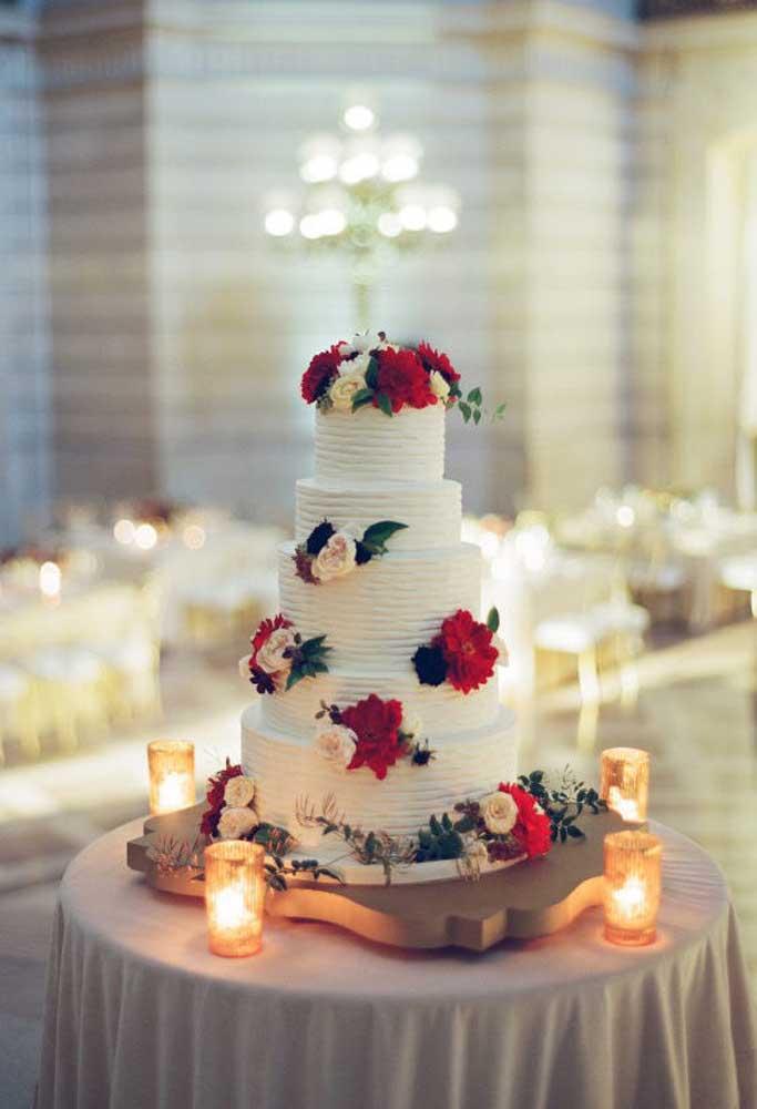 O bolo de casamento fica mais bonito quando colocado em uma mesa sozinho. Nesse caso, foi usado apenas alguns copos com velas para decorar o espaço, pois o destaque ficou mesmo nos arranjos florais do bolo.