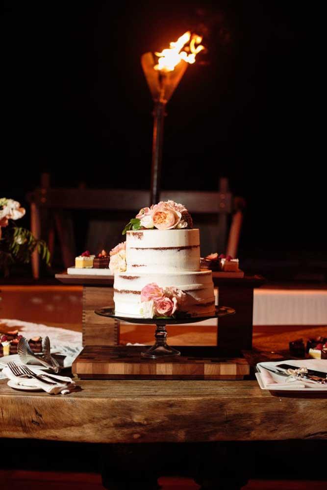 Escolha uma grande mesa de madeira e coloque o bolo bem no centro. Use a mesma mesa para servir os pratos dos convidados. A iluminação feita com tocha deixa o ambiente mais intimista.