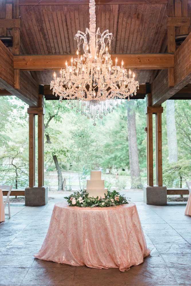 O luxo dessa decoração nem está na mesa de bolo de casamento, mas no lustre que está suspenso sobre a mesa. Isso faz com que chame mais atenção do bolo.