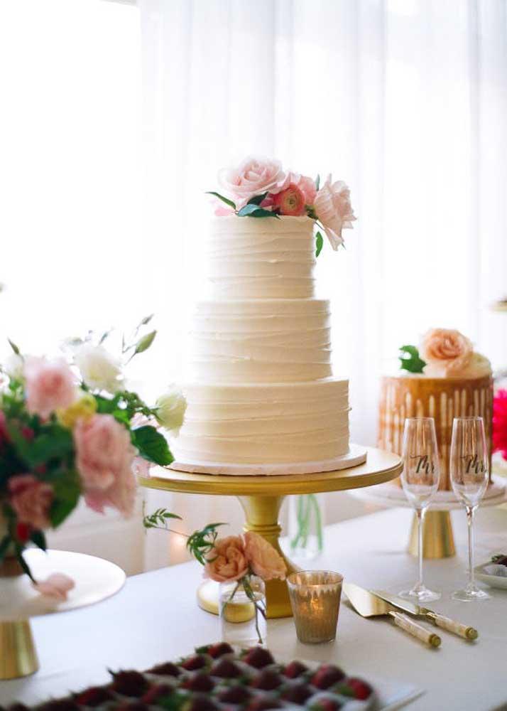Faça um bolo de três andares com a textura totalmente lisa para o casamento. Apenas acrescente um arranjo de flores no topo do bolo.