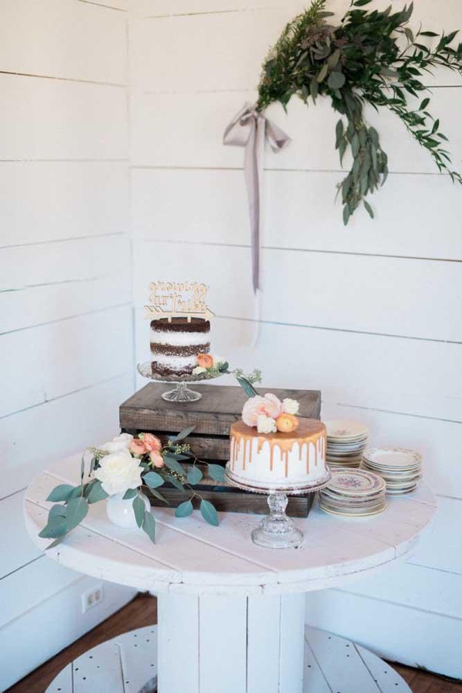 Aqui o bolo de casamento foi colocado em cima de algumas caixas de madeira. Na mesa, apenas um arranjo de flores para decorar.