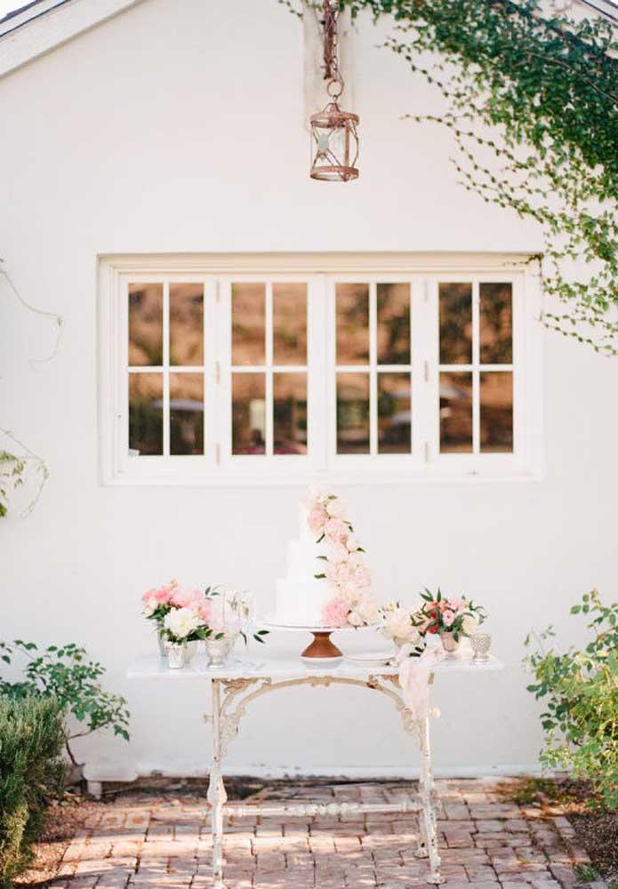 Use uma pequena mesa para colocar o bolo de casamento. Decore o bolo com arranjo de flores e use o mesmo tipo de flor para decorar os vasos.