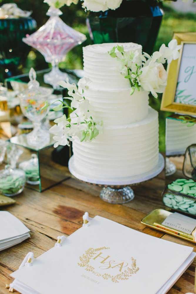 Use vários elementos que fazem referências ao tema para decorar a mesa de bolo de casamento.