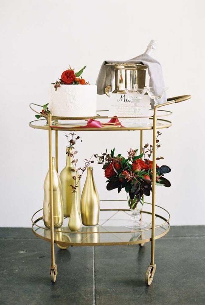 Sabe aquelas mesas que servem bebidas? Você pode usar uma mesa nesse modelo para colocar o bolo de casamento. Ao lado coloque um champagne com as taças para os noivos brindarem.