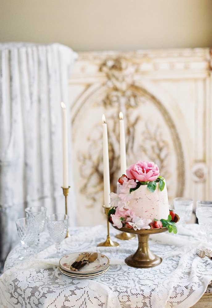 Arrume a mesa com uma toalha de renda e coloque o bolo em cima. Para decorar, apenas use alguns castiçais com velas e taças de cristais.