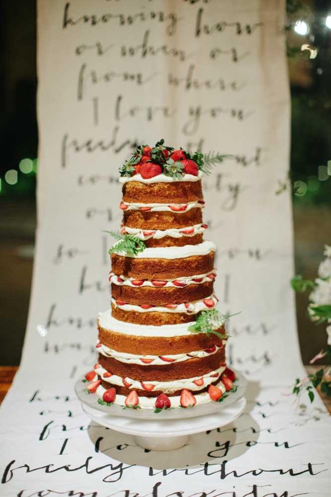 Você já viu um naked cake desse tamanho? Pois bem, esse foi feito para seguir a tradição do bolo de noiva de andares. A mesa é de madeira e para decorar, apenas uma faixa com mensagens.