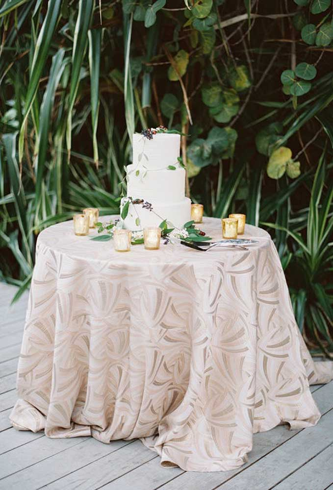 Um bolo simples e barato para casamento pode ser feito usando pasta americana e não precisa fazer muitos andares. Decore a mesa com velas e uma linda toalha.