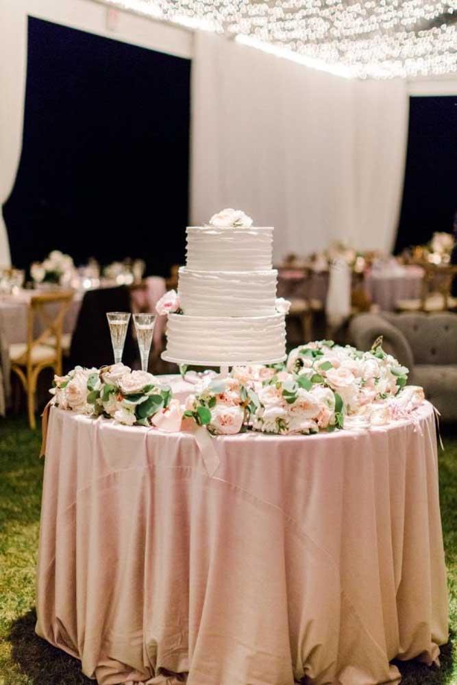 Siga o mesmo modelo de mesa da festa na hora de colocar o bolo do casamento. Apenas faça uma decoração com flores para deixar o ambiente mais delicado.