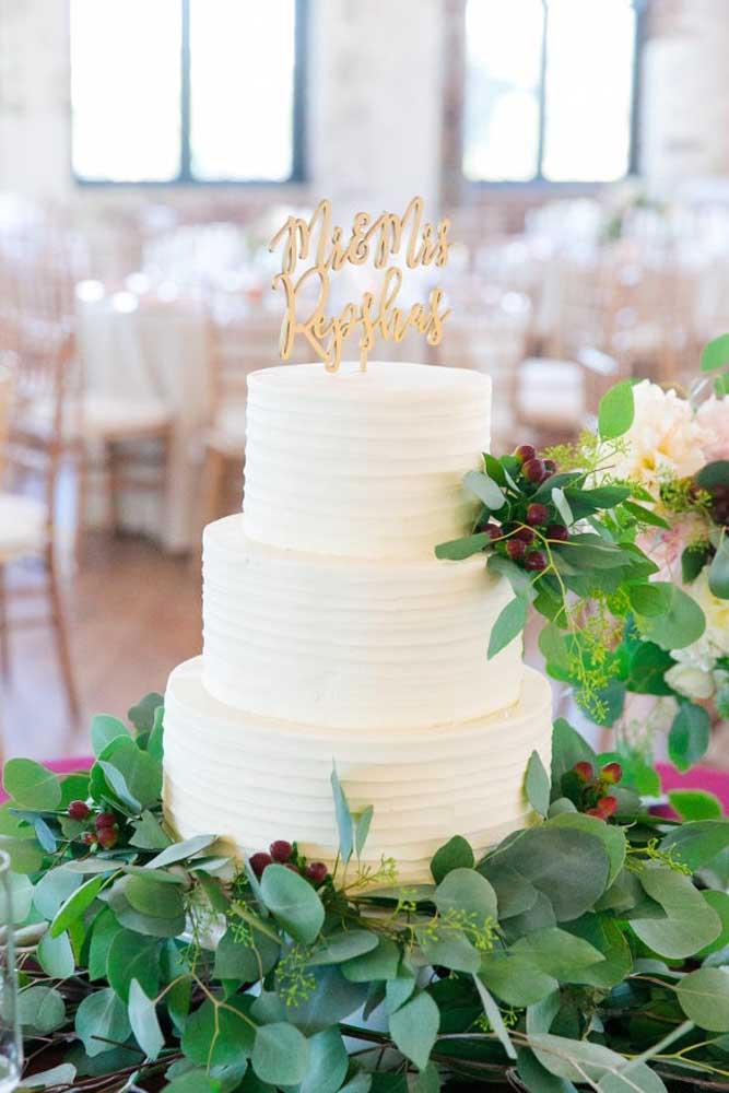 Folhas e flores artificiais são perfeitas na hora de decorar a mesa do bolo de casamento.