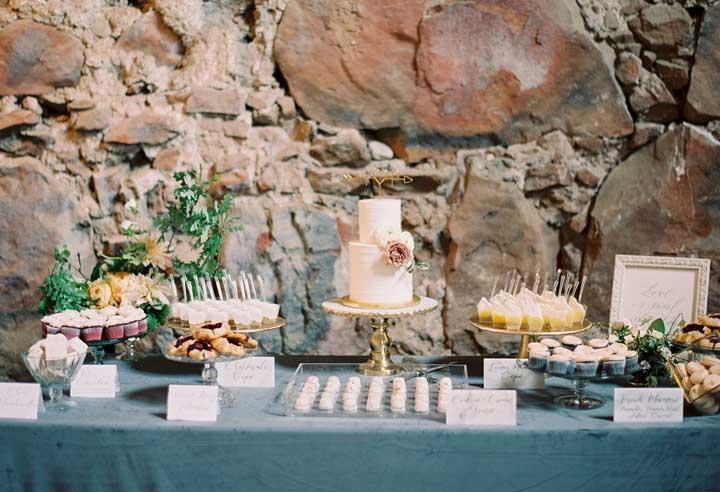 Olha o efeito da decoração dessa mesa quando colocada na frente de uma parede feita toda de pedra.