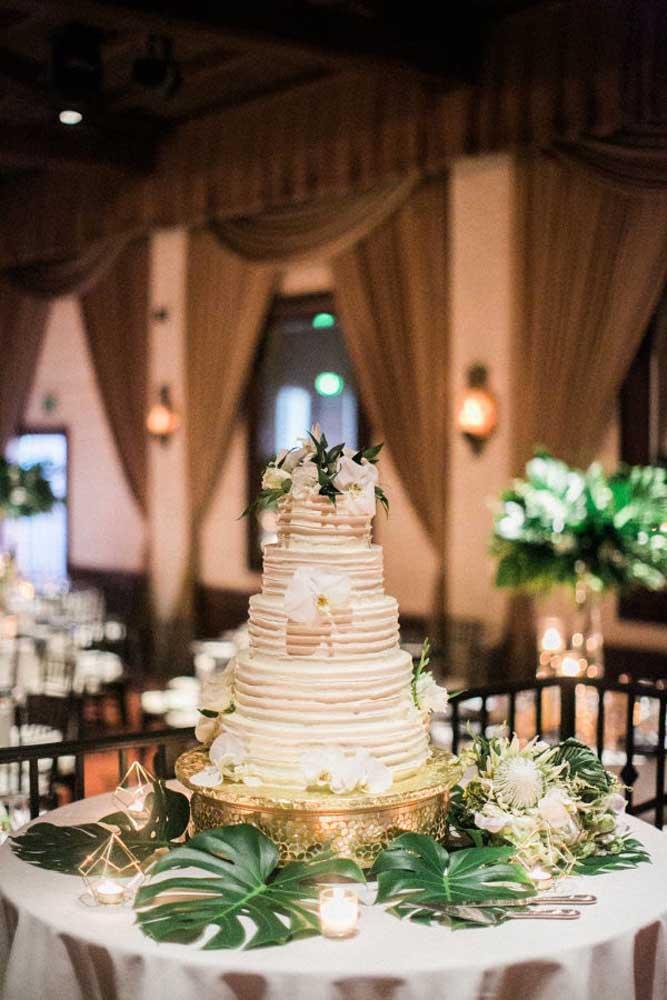 Uma boa decoração para a mesa do bolo de casamento é usar algumas folhas grandes e acrescentar algumas velas ao redor. Mas capriche na base onde será colocado o bolo.